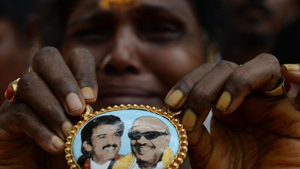 A DMK party supporter cries as she displays a locket with a portrait of party president M Karunanidhi n front of hospital where he is being treated in Chennai.