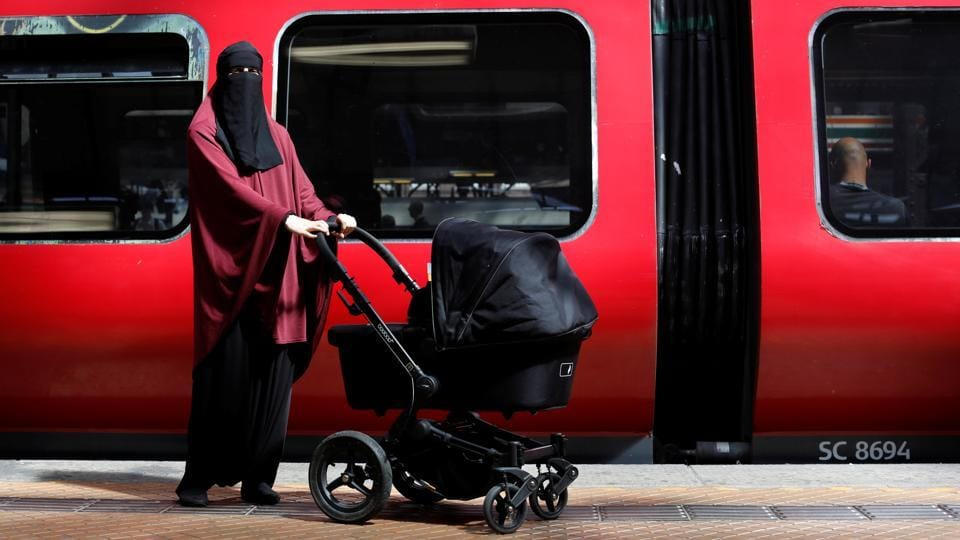 Sarah, 30, poses for a portrait. She stands at the spot, where she said, a man screamed anti-Islamic obscenities at her while almost forcing her onto the train tracks as she cradled her then two-week-old baby. (Andrew Kelly / Reuters)