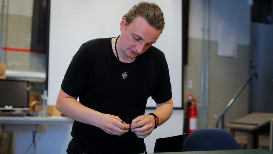 "Mathias Vidas Olsen, 29, a viking-age replica jewellery maker, demonstrates the preparation of bracelets he designed with a phrase that translates to ""I will go with the burqa, will you?"" in Copenhagen. ""I'm not for or against the niqab,"" Olsen said. ""I'm for the right of the people to wear whatever they want whether they be a Muslim or a punk,"" he added. (Andrew Kelly / Reuters)"