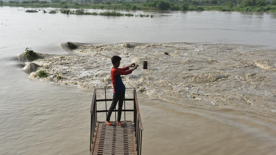 The water level of Yamuna river in the national capital is expected to rise further as 21,006 Cusec of water has been released from the Hathani Kund Barrage on Tuesday night.  The rising water levels which is threatening to breach its bank has forced more than 10,000 people to take refuge on higher ground. (Raj K Raj / HT Photo)