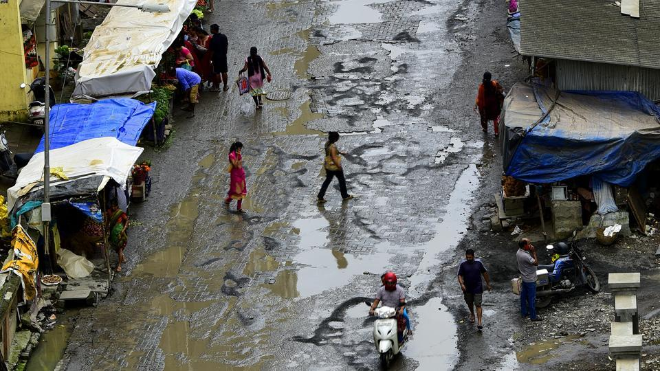 Motorists dodge potholes on a road in Sion, which deteriorated after a month of showers.