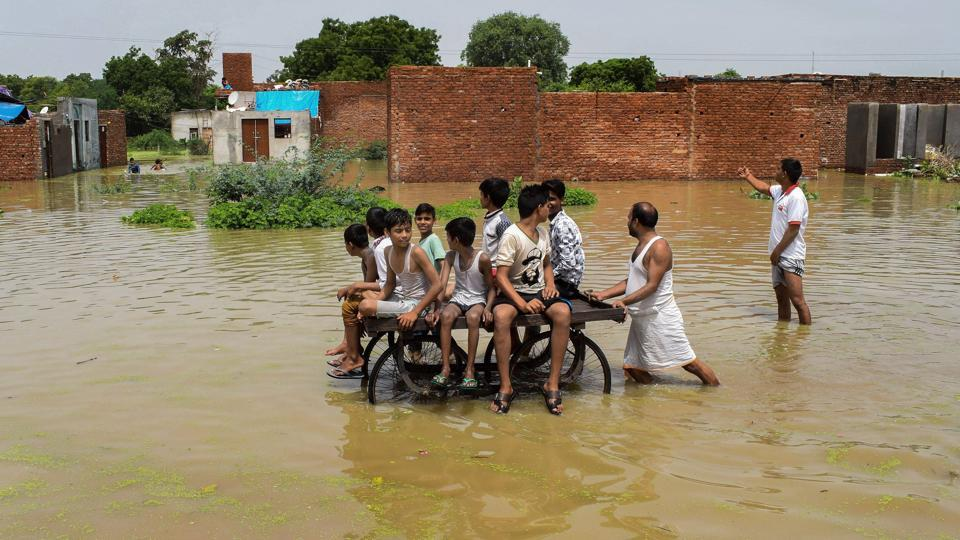 Children ride a cart as they move through a flooded colony, inundated by the Yamuna river, in Mathura on Thursday. (PTI)