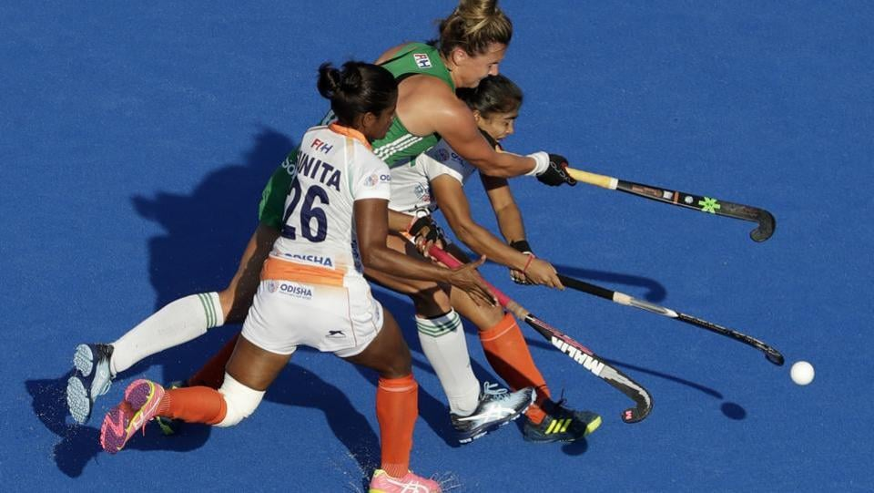 Sunita Lakra (L), competes for the ball with Ireland's Nicola Evans (C), during the Women's Hockey World Cup quarterfinal match between India and Ireland at the Lee Valley Hockey and Tennis Centre in London, England on August 02, 2018. (Matt Dunham / AP)