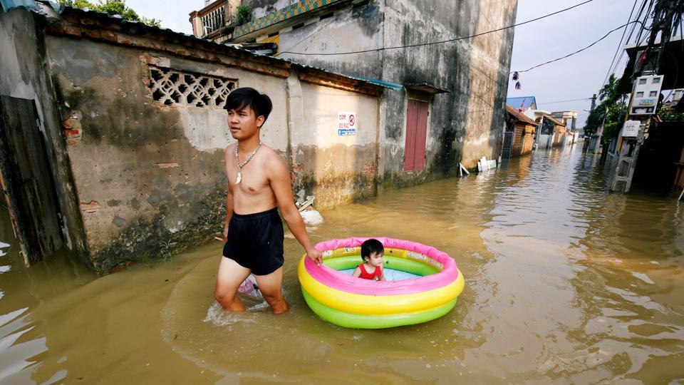 A man pulls an inflatable pool carrying his daughter on a flooded village after heavy rainfall caused by tropical storm Son Tinh outside Hanoi, Vietnam. (Kham / REUTERS)