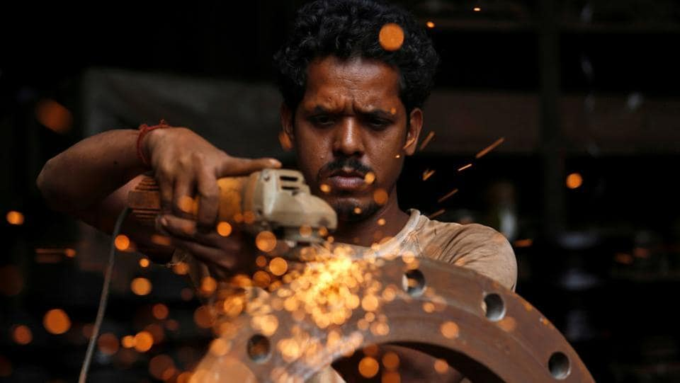 A man uses a disc grinder as he smoothens a flange ring at a workshop in an industrial area in Mumbai, Maharashtra on August 2, 2018. (Francis Mascarenhas / REUTERS)