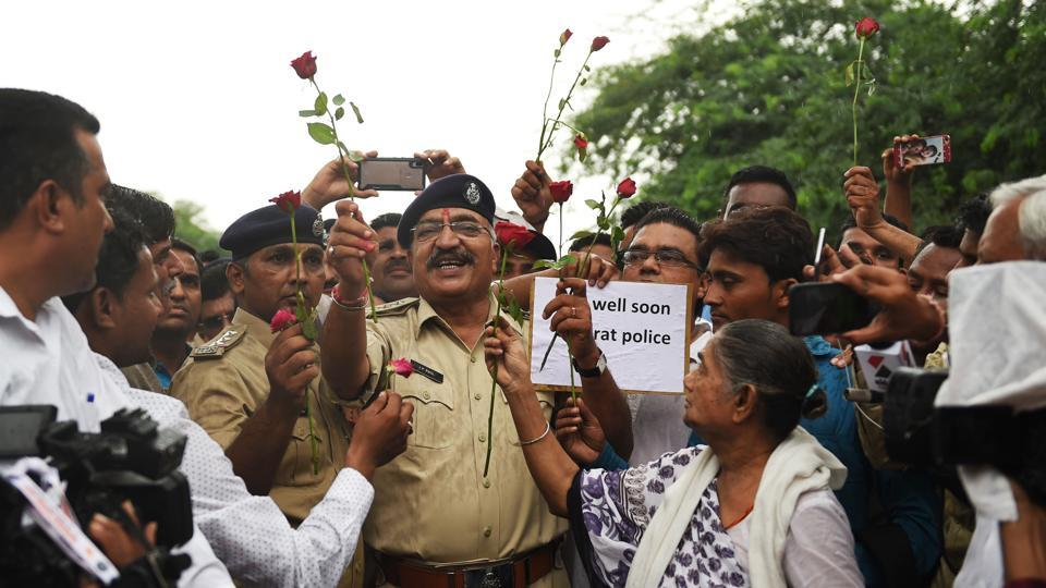 Senior Police officers receive roses from members of the Chhara community, who are originally listed under the Criminal Tribes Act of 1871, at Kubernagar Police Chowky on the outskirts of Ahmedabad, Gujarat following a dispute with policemen on July 27 that turned violent on July 29, 2018. (Sam Panthaky / AFP)