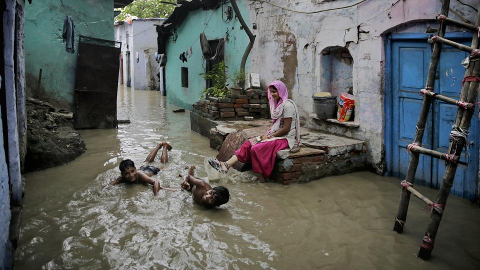 Boys play in flood waters outside their submerged home by the banks of the Yamuna in New Delhi on July 31, 2018. (Altaf Qadri / AP)