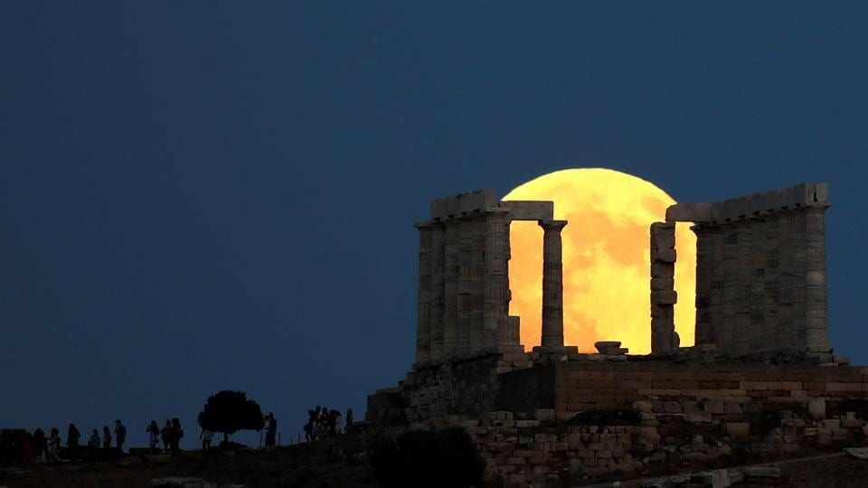 People watch a full moon rising behind the Temple of Poseidon before a lunar eclipse in Cape Sounion, near Athens, Greece. (Alkis Konstantinidis / REUTERS)