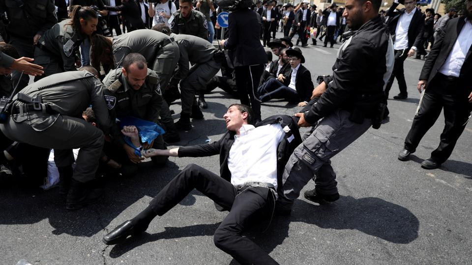 Israeli police scuffle with an ultra-Orthodox Jewish man as he takes part in a protest against the detention of a fellow community member who evaded a military draft order, in Jerusalem, Israel. (Ammar Awad / REUTERS)
