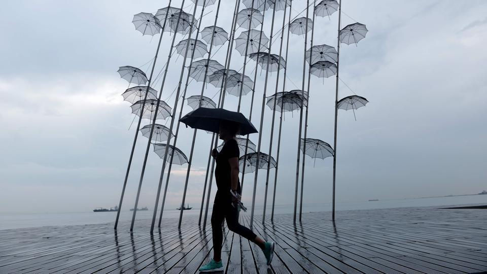 A woman with an umbrella walks under the rain past a sculpture called 'Umbrellas' by Greek sculptor George Zongolopoulos along the waterfront in Thessaloniki, Greece. (Sakis Mitrolidis / AFP)