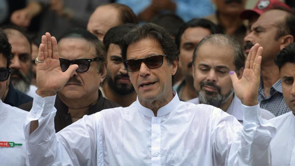 Pakistan's cricketer-turned politician Imran Khan speaks to the media after casting his vote at a polling station during the general election in Islamabad on July 25.