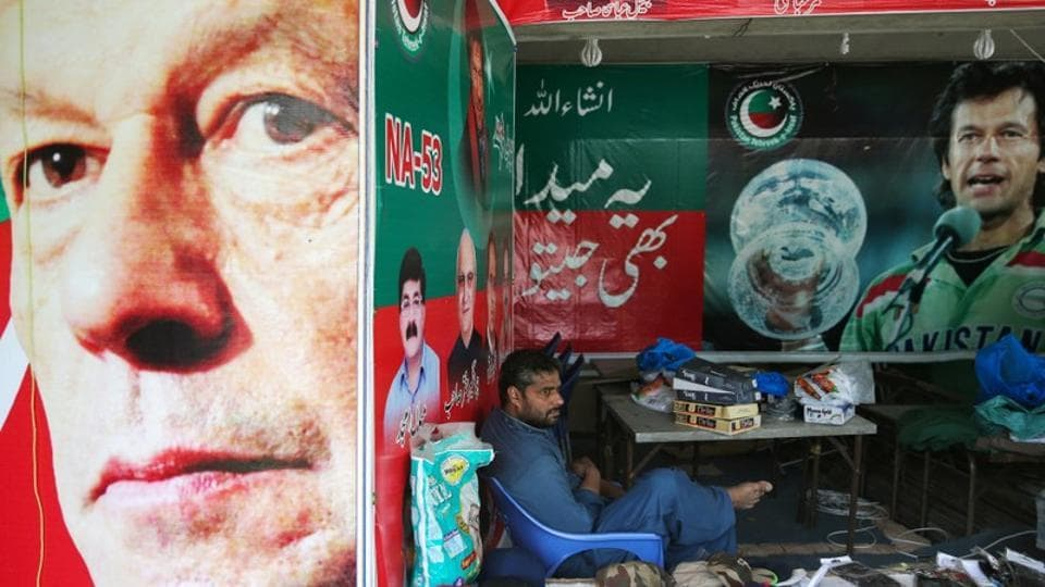 A vendor sits next to images of cricket star-turned-politician Imran Khan, chairman of Pakistan Tehreek-e-Insaf (PTI) at a market in Islamabad, Pakistan.