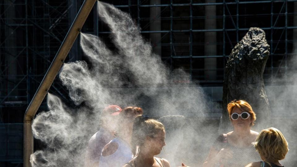 People cool off under water sprays in Lille, northern France. Temperatures passed 40 C in France for the first time this summer on Friday as millions hit the roads for August vacations, with sweltering conditions forecast to persist into next week. (Philippe Huguen / AFP)