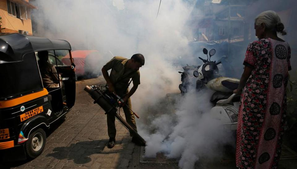 A municipal worker fumigates a manhole in a street to prevent the spread of dengue fever and other mosquito-borne diseases in Mumbai.