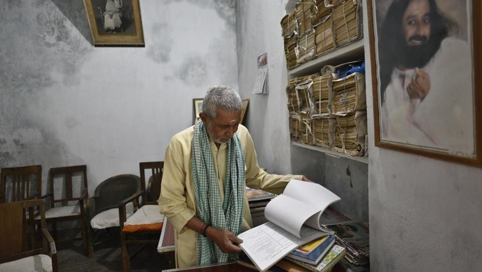 Bhairav Nath Shukla, has been Mukti Bhavan's manager for the last 40 years. Shukla hosts people when they are close to death, allocating one of the Bhavan's 10 rooms to them and supervises the transition from material to immortal. He has done this more than 12,000 times. Piles of hard-bound registers recording these details, smelling of seepage, sit stacked besides him. (Sanchit Khanna / HT Photo)