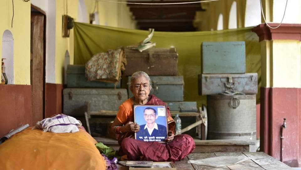 Saraswati Aggarwal holds a picture of her late husband at Mumukshu Bhavan. This landmark near the iconic Assi Ghat is spread over four acres. The campus has a secondary school, temple, resthouse for travellers and a 60-room section for salvation-seekers. (Sanchit Khanna / HT Photo)