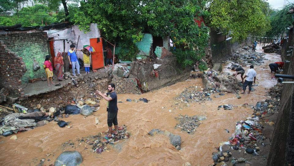 People inspect damage caused by flash floods following heavy rains at Kalka Colony, in Jammu. Heavy rain was reported in northern districts of Haryana, including Karnal, Yamunanagar, Kaithal and Kurukshetra. Rains in the last 24 hours have triggered landslides in several places across Himachal Pradesh. More than 100 lateral roads in the state were closed after being damaged by landslides. (PTI)