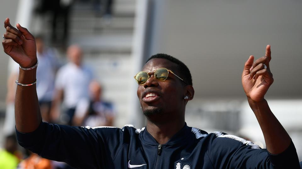 France's midfielder Paul Pogba celebrates with teammates after disembarking from the plane upon their arrival at the Roissy-Charles de Gaulle airport on the outskirts of Paris.