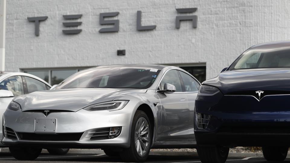 2018 Model 3 sedan sits next to a Model X on display outside a Tesla showroom in Littleton, Colo.