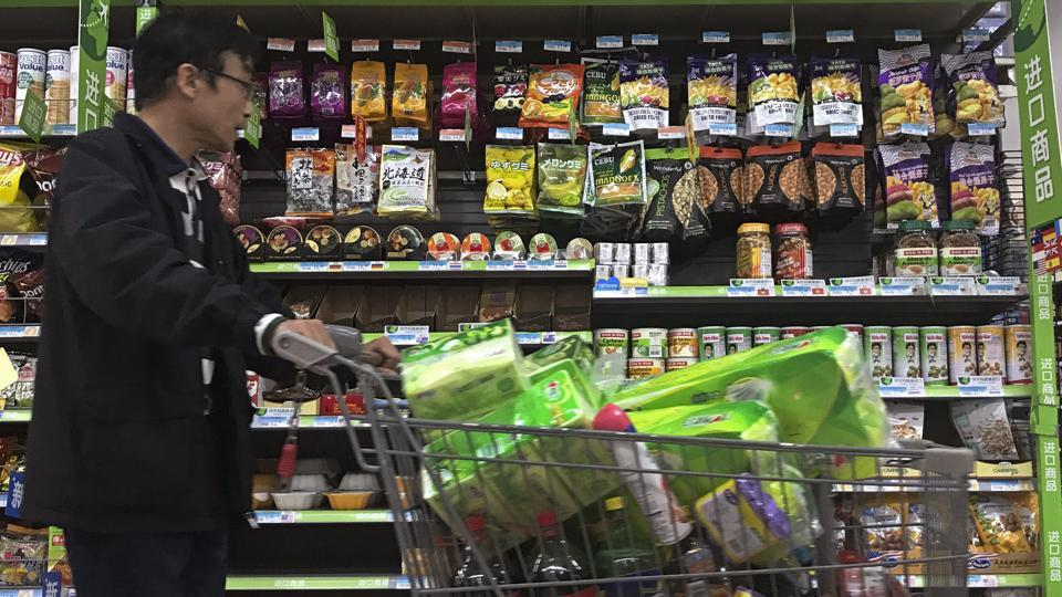 A man pushes a shopping cart past a display of nuts imported from the United States and other countries at a supermarket in Beijing. China confirmed that it will impose 25 percent tariffs on an additional $16 billion worth of imports from the US from August 23, 2018.