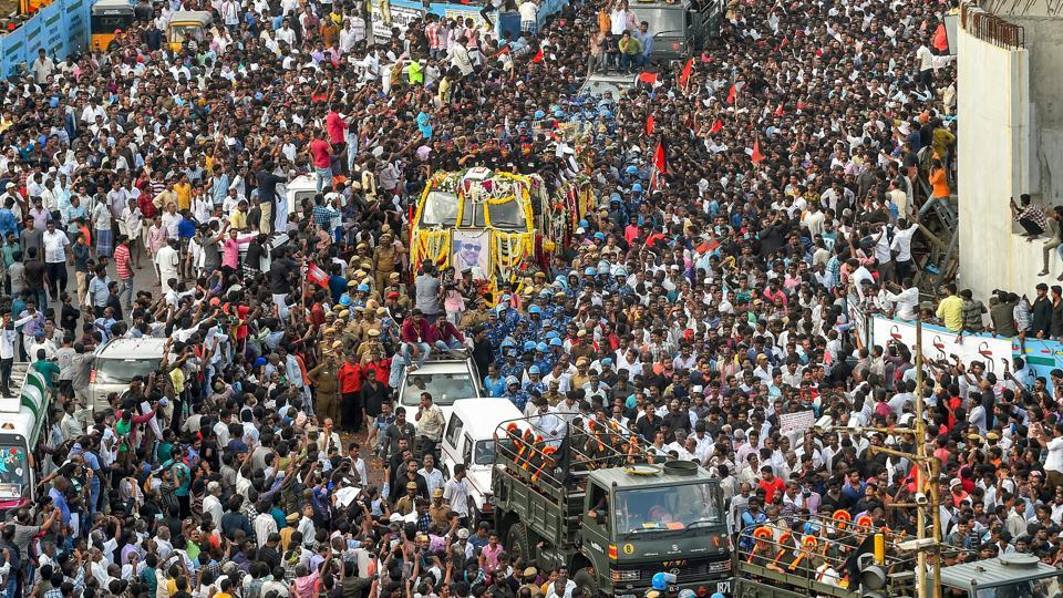 People gather to pay their last respects to DMK chief M Karunanidhi as his cortege passes through the streets of Chennai. (PTI Photo)