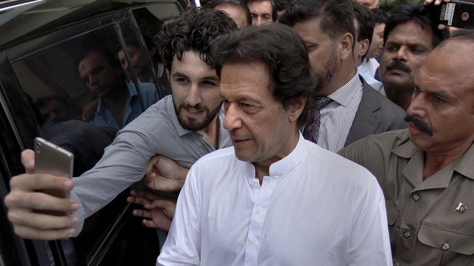 A Pakistani takes selfie with Imran Khan, center, head of the Pakistan Tehreek-e-Insaf party, as he leaves a party meeting in Islamabad, Pakistan, Monday, Aug. 6, 2018.