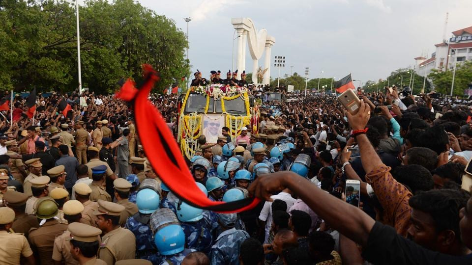 Supporters wave as a vehicle carrying a glass casket with body of DMK party president M Karunanidhi approaches during the funeral procession, in Chennai. (AFP Photo)