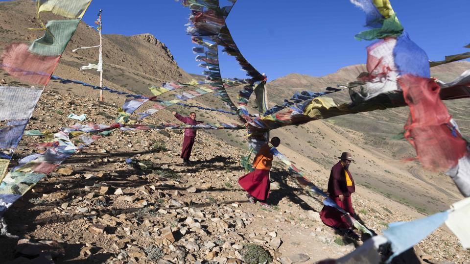 Buddhist monk Nawang Tashi (R), 53, and others walks past prayer flags atop a hill overlooking Tnagyud Gompa Buddhist monastery in Komik, Spiti Valley in Himachal Pradesh. Some 5,500 metres (18,000 feet) above sea level in the Indian Himalayas sits the Tnagyud Gompa Buddhist monastery, where snow can leave the monks in complete isolation for seven months a year. (Xavier Galiana / AFP)