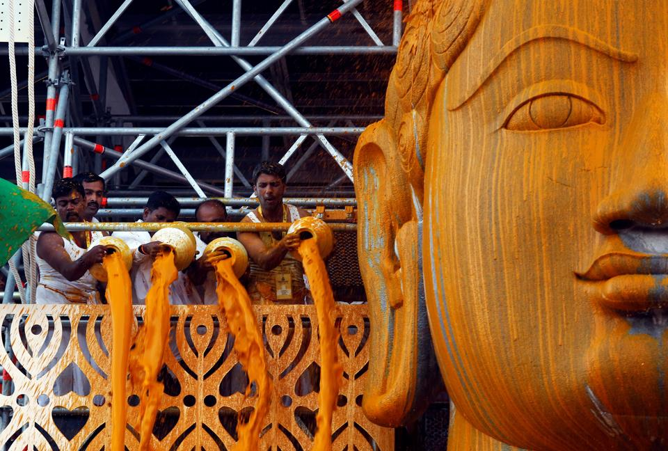 Devotees pour turmeric paste on the statue of Jain god Gomateshwara during a ceremony, Shravanabelagola, February 17