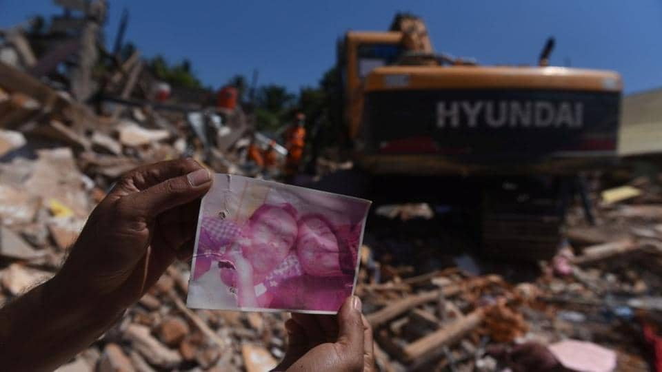 A resident shows a photo of missing victims believed to be trapped inside a collapsed building, as rescue workers continue searching after Sunday's earthquake in Pemenang, North Lombok, Indonesia. Another aftershock rocked Indonesia's Lombok on Thursday, sparking fresh panic on the tropical tourist island after a series of tremors in the past two weeks. (Zabur Karuru / Antara Foto / REUTERS)