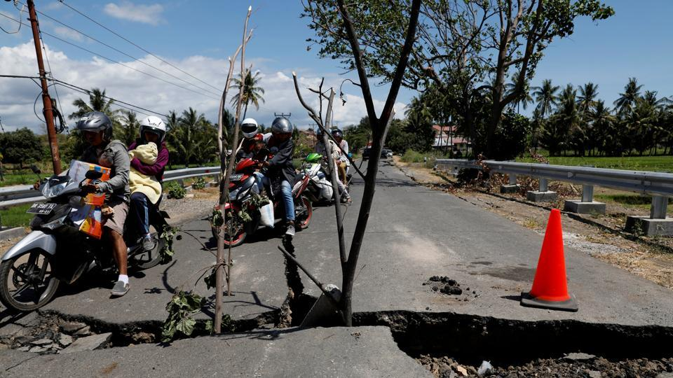 Motorcycles pass a cracked road at Kayangan district in North Lombok. Officials said about three-quarters of Lombok's rural north had been without electricity since Sunday, although power had since been restored in most areas. Aid workers have found some hamlets hard to reach because bridges and roads were torn up by the disaster. (Beawiharta / REUTERS)