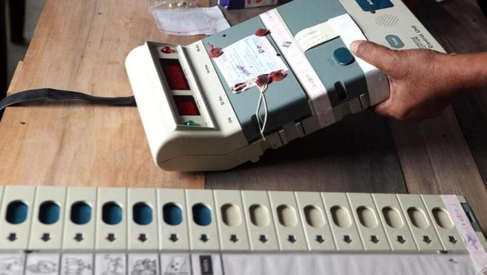 Election Commission officials seal an Electronic Voting Machine (EVM) prior to the start of voting at a polling station.