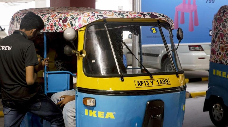 A worker stands next to an Ikea branded auto-rickshaw during the launch of the company's store in Hitech City on the outskirts of Hyderabad, India, on Wednesday, Aug. 8, 2018.
