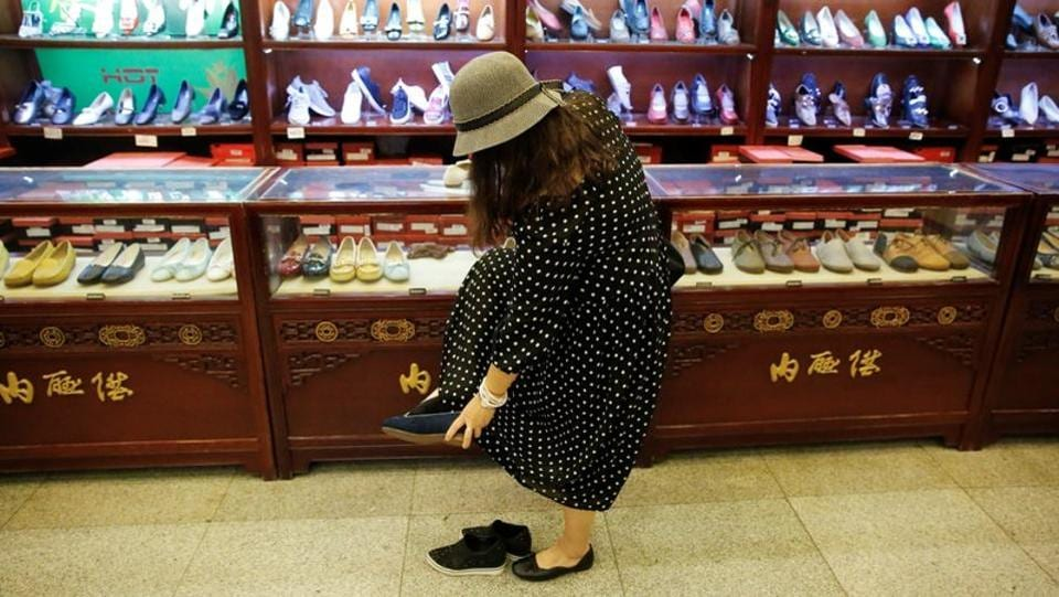 A customer tries on a handmade 'thousand-layer' cloth shoe at the Neiliansheng showroom. Thousand layer shoes as part of women's wardrobes is a far more recent concept, emerging with the establishment of the modern People's Republic of China. (Thomas Peter / REUTERS)