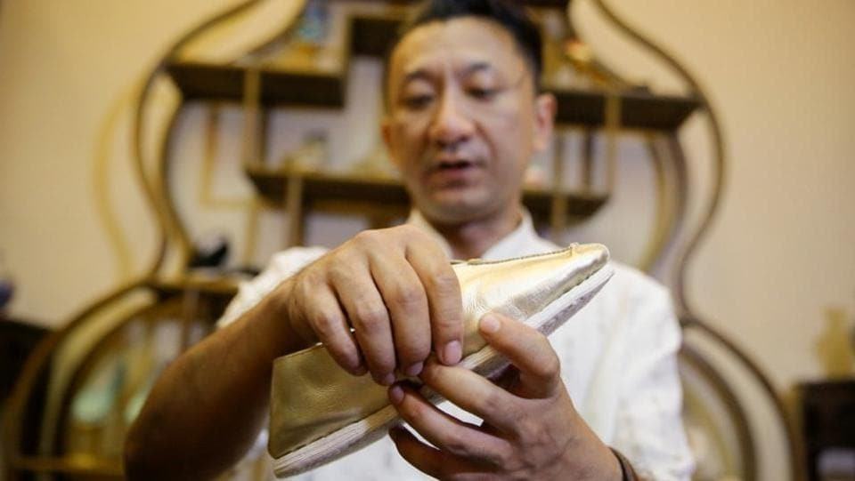"""To make good shoes, one needs qualities such as conscientiousness, persistence and concentration,"" said Cai as he sat at a small table, finishing off another pair.  (Thomas Peter / REUTERS)"