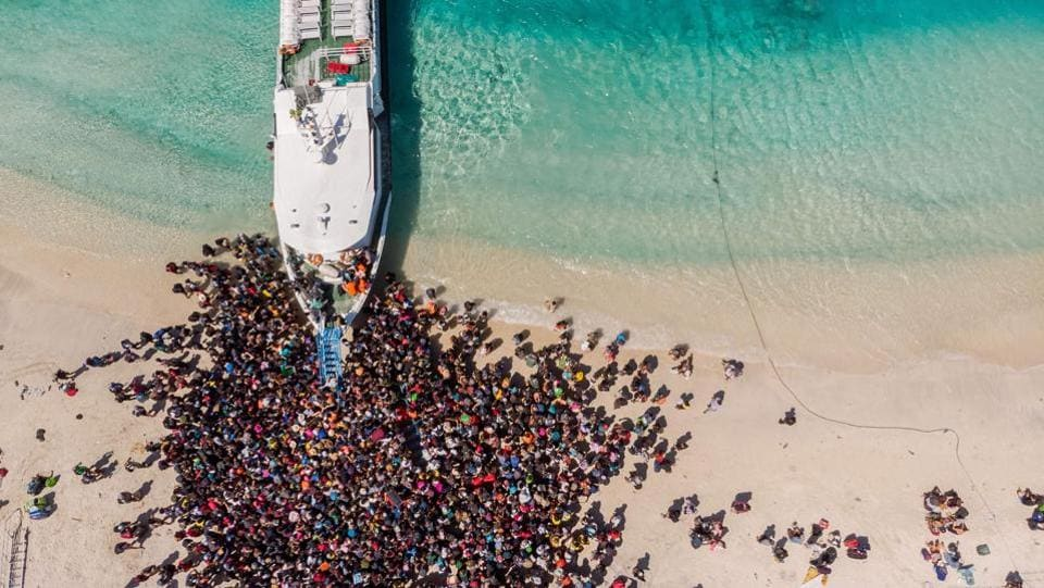 People crowd the beach as they wait to be evacuated from Gili Trawangan island. Thousands of tourists have left Lombok since Sunday, fearing further earthquakes, some on extra flights provided by airlines and others on ferries to the neighbouring island of Bali. (Melissa Delport / @trufflejournal / AFP)
