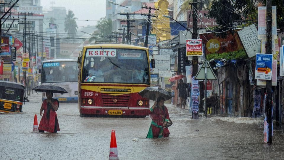 Pedestrians and commuters wade through a flooded street during monsoon rainfall, in Thiruvananthapuram on Tuesday, July 31, 2018.