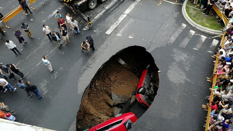 People gather near the scene where two vehicles have fallen into a sinkhole on a street in Harbin, Heilongjiang province, China. (REUTERS)