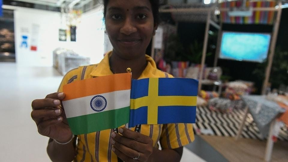 A worker holds flags of India and Sweden during the opening ceremony of the new IKEA store in Hyderabad. (Noah Seelam / AFP)