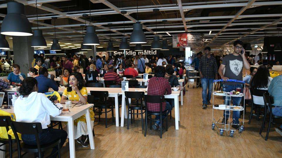 "Customers eats at a restaurant at the new IKEA store in Hyderabad. To try and ensure it recoups its $1.5-billion investment, the Swedish company has tweaked its offerings to suit Indian tastes, starting with the restaurant, where ""Smaklig Maltid -- 'Enjoy your Meal' in Swedish"" is written on the wall. (Noah Seelam / AFP)"