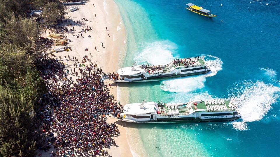 People crowd the beach as they wait to be evacuated from Indonesia's Gili Trawangan island to neighbouring Lombok island a day after a 6.9 magnitude earthquake struck the area. (Melissa Delport / @trufflejournal / AFP)
