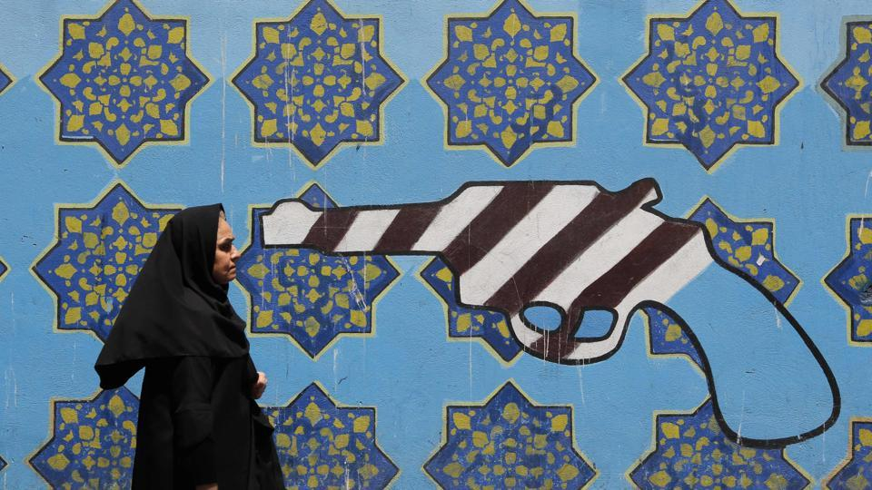 An Iranian woman walks past a mural depicting a gun painted on the wall of the former US embassy in the capital Tehran. (Atta Kenare / AFP)