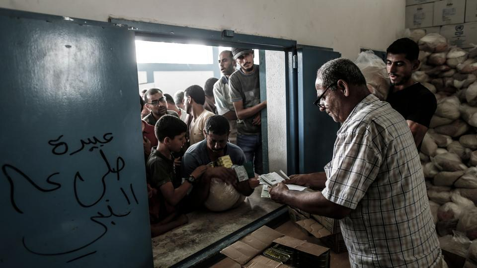 Palestinians receive aids at a United Nations food distribution centre in Jabalia refugee camp in the northern Gaza Strip. (Mahmud Hams / AFP)