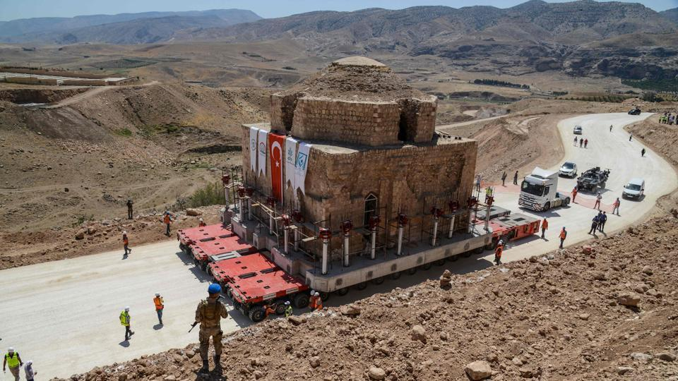 A Tukish soldier stands guard as the Artuklu Hamam, a centuries-old bath house weighing 1,600 tonnes, is loaded onto a wheeled platform an moved down a specially constructed road from the southeastern town of Hasankeyf to a new location to avoid being engulfed under floodwaters by a controversial dam project. (Ilyas Akengin / AFP)