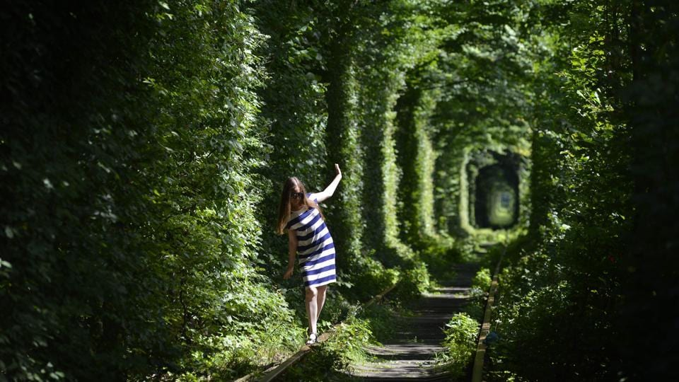 A girl walks along former railway tracks in the so-called 'Tunnel of Love', surrounded by arches of intertwined trees, near the Ukrainian village of Klevan, Rivno region. (Sergei Supinsky / AFP)