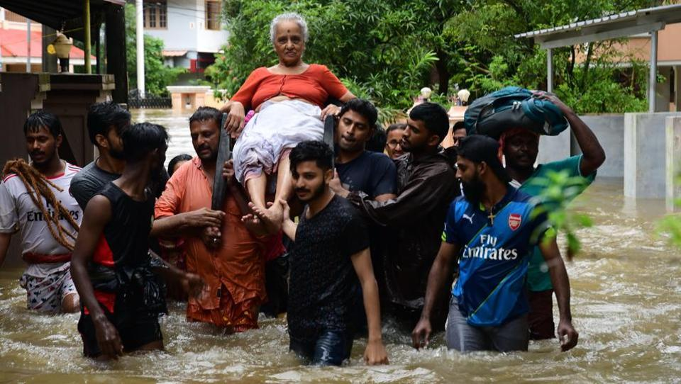 An elderly woman being rescued by residents after a flash flood hits Palakkad, Kerala. (PTI)