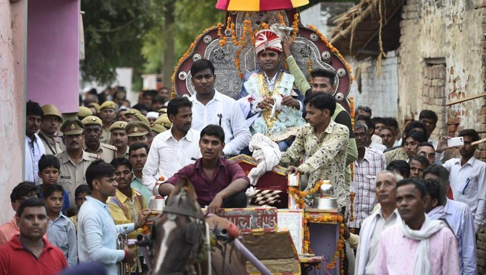 Sanjay Jatav (C), 27, is escorted by the police as he reaches his bride's village in Nizampur with his wedding procession on July 15, 2018 in Kasganj, Uttar Pradesh. Jatav's wedding became grander as the day loomed closer, from the number of cars in his baraat (finally fixed at 100) to the number of VIPs in his guest list. He hadn't always planned on a spectacle however. (Burhaan Kinu / HT Photo)