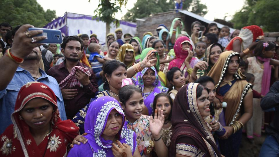 "Family members of the bride welcome the incoming wedding procession. As Jatav's convoy entered the village, greeted by a phalanx of press, senior police and administration officers and political leaders cutting across party lines, even the Thakur families left everything they were doing and rushed to their rooftops to witness the breach of the village ""tradition"". (Burhaan Kinu / HT Photo)"