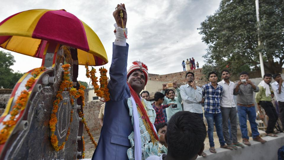 "Dressed in a powder-blue suit tailored in Aligarh, Jatav arrived in a pristine white car followed by an armed bodyguard and holding a filigreed dagger in his hands. He grew more and more excited as his vehicle approached Nizampur. One moment he declared that he looked as lavish ""as a Thakur""; the next moment he said he felt like a ""cabinet minister."" (Burhaan Kinu / HT Photo)"
