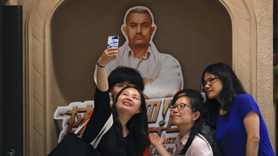 Chinese women take a selfie with a poster of Indian Bollywood blockbuster film